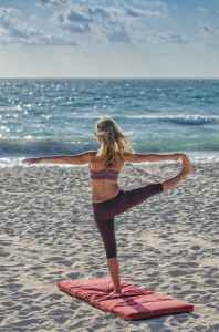 Woman does yoga on a beach